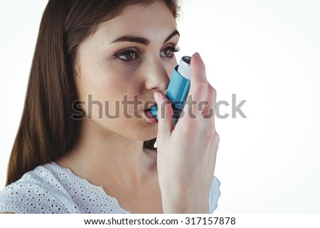 Asthmatic brunette using her inhaler on white background - stock photo