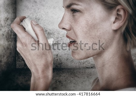 Asthmatic pretty blonde woman using inhaler against image of room corner - stock photo