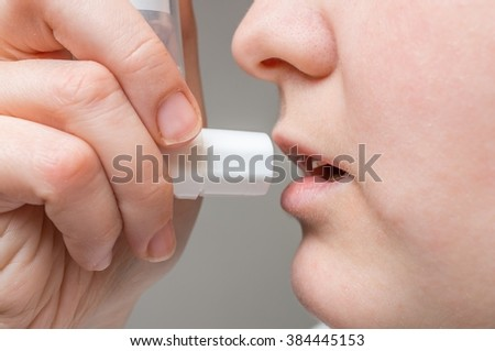 Asthmatic woman is using inhaler.