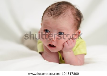 Astonished Baby Boy. One month old infant boy holding his head in his hands with a surprised look on his face. Shallow DOF. - stock photo