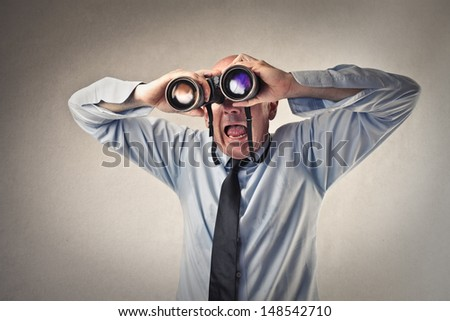 astonished businessman looking with binoculars - stock photo