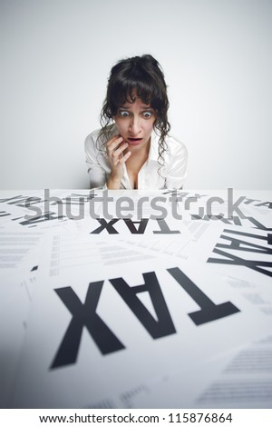 Astonished businesswoman looking at a bunch of worrying tax forms on her desk - stock photo