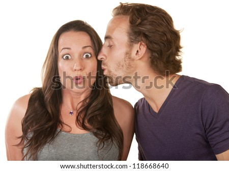 Astonished Caucasian woman kissed on cheek by man