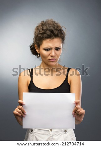 astonished girl with brown curl hair holding white blank on grey-light background - stock photo