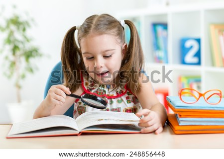 Astonished kid looking through a magnifying glass with book at home - stock photo