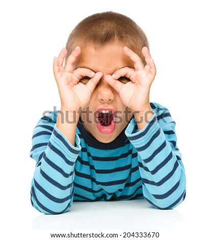 Astonished little boy is showing glasses gesture, isolated over white - stock photo