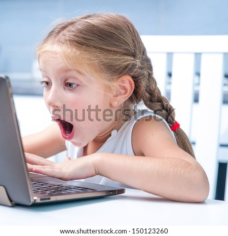 astonished little girl with her computer at home at the table - stock photo