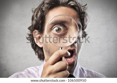 Astonished man looking through a magnifying glass - stock photo