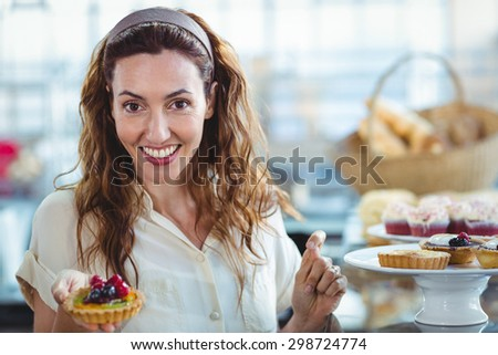 Astonished pretty woman looking at camera in the bakery