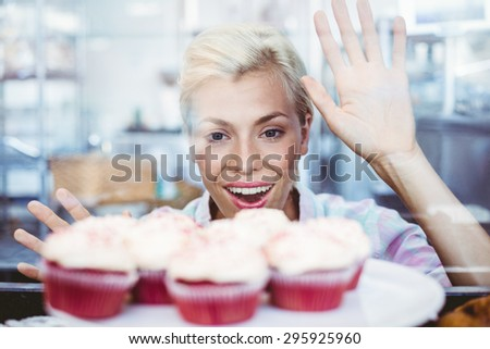Astonished pretty woman looking at cup cakes at the bakery - stock photo