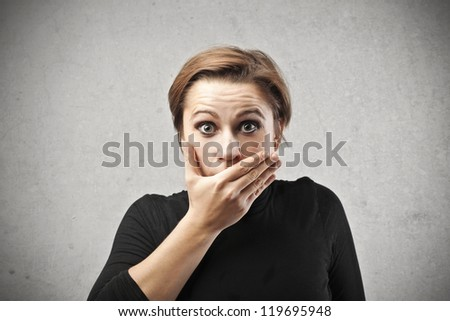 Astonished woman covering her mouth with her right hand - stock photo