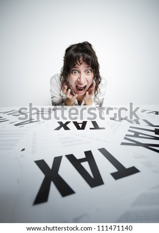 Astonished woman looking at a bunch of worrying tax forms on her desk - stock photo