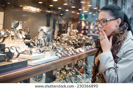 Astonished woman looking to showcase or shop window. Surprised shopping girl chooses jewelry in store - stock photo