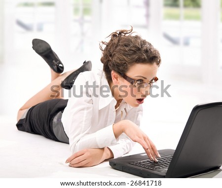 Astonished young businesswoman with laptop on the floor - stock photo
