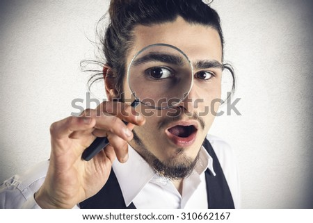 Astonished young man looks through a magnifying lens