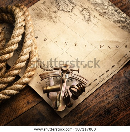 Astrolabe and rope on vintage map. Adventure stories background. - stock photo