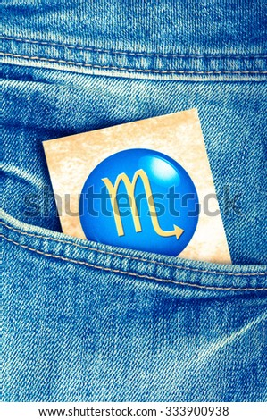 astrology card with sign of scorpion in a blue jeans pocket - stock photo