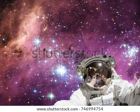 Astronaut and galaxy on the backdrop. The elements of this image furnished by NASA.