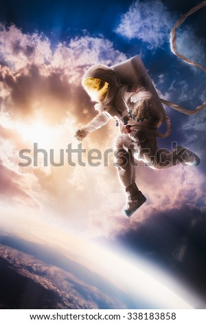 Astronaut floating in the stratosphere near a planet - stock photo