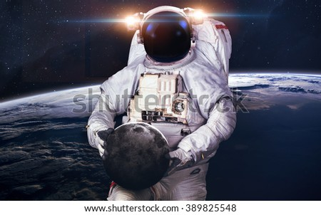 Astronaut holding planet. Elements of this image furnished by NASA
