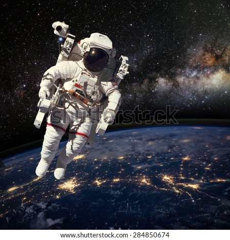 Astronaut in outer space above the earth during night time. Elements of this image furnished by NASA. - stock photo