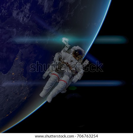 Astronaut in outer space. Planet Earth on the background. Elements of this image furnished by NASA.