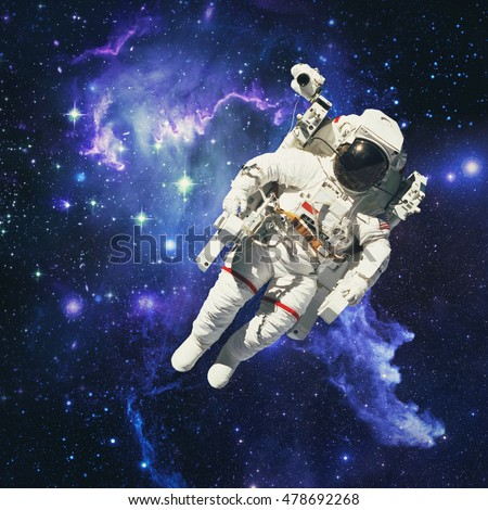 Astronaut in outer space with galaxies and gas in the background. Elements of this image furnished by NASA.