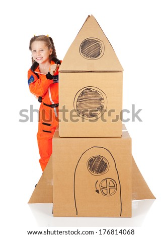 Astronaut: Little Girl Behind Cardboard Rocket - stock photo