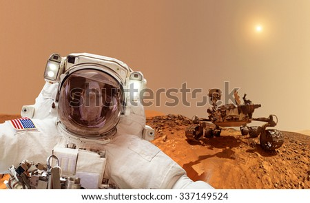 Astronaut on Mars in background a rover - Elements of this image furnished by NASA - stock photo