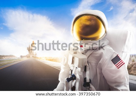 Astronaut standing on a road with space shuttle on the horizon - stock photo