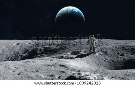 Astronaut stay on the Moon surface against Earth on the background, Exploring space and other planets