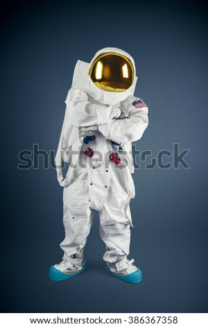 Astronaut with his arms crossed on a grey background - stock photo
