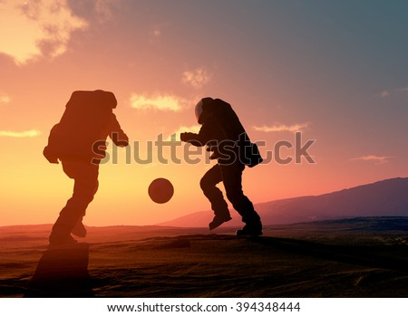 Astronauts are playing football on the planet. - stock photo