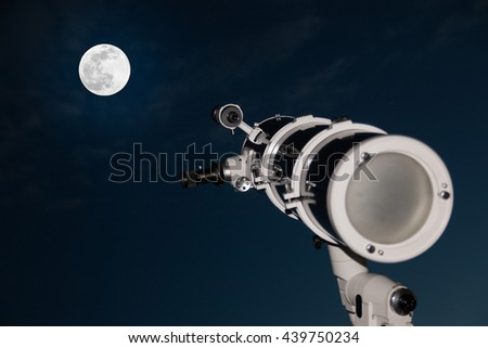 Astronomical telescope over dark sky with the moon in the night - stock photo
