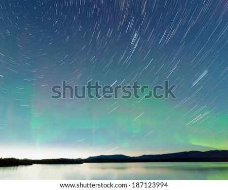 Astrophotography star trails on midsummer night sky with Aurora borealis or Northern Lights over calm water surface of Lake Laberge, Yukon Territory, Canada - stock photo