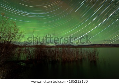 Astrophotography star trails with glowing green night sky from Aurora borealis or Northern Lights over shore willow bush at Lake Laberge, Yukon Territory, Canada - stock photo