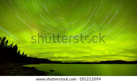 Astrophotography star trails with green glowing display of Aurora borealis or Northern Lights over boreal forest taiga at Lake Laberge, Yukon Territory, Canada - stock photo