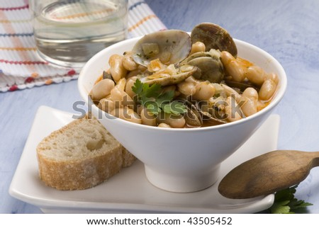 Asturian clams and beans stew served in a white bowl. Spanish cuisine. Selective focus. Fabes con almejas.