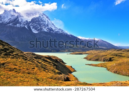 Asure Lake Pehoe water at the foot of the magnificent snow-covered cliffs of Los Kuernos. National Park Torres del Paine, Chile - stock photo