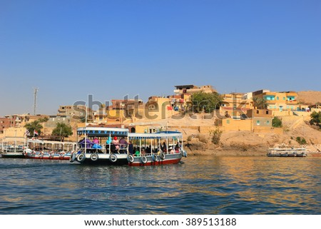 ASWAN, EGYPT - FEBRUARY 1, 2016: Wooden boats carrying passengers along the Nile River in Egypt, North Africa - stock photo
