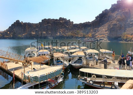 ASWAN, EGYPT - FEBRUARY 1, 2016: Wooden boats carrying passengers docked along the Nile River at the Temple of Philae  in Egypt, North Africa