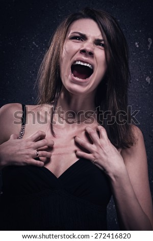 Asylum. Screaming crazy woman. Low key. - stock photo