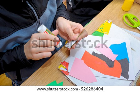 At a lesson of the fine arts. The school student does abstract application, of multi-colored sheets of paper