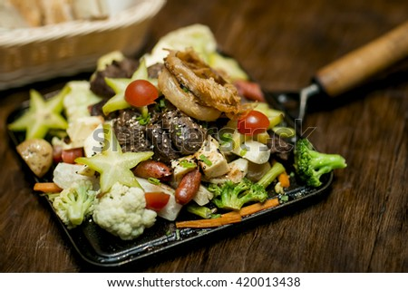 at and vegetables served on a cast iron plate on a wooden table