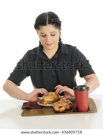 At attractive teen girl preparing to enjoy a fast food breakfast containing a bangle breakfast sandwich, fritter and coffee.  On a white background. - stock photo