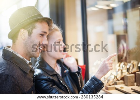 At Christmastime in the city a young trendy couple looking at watches in a showcase - stock photo