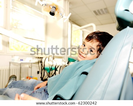 At dentist's modern working place, cute kid sitting on chair and smiling - stock photo