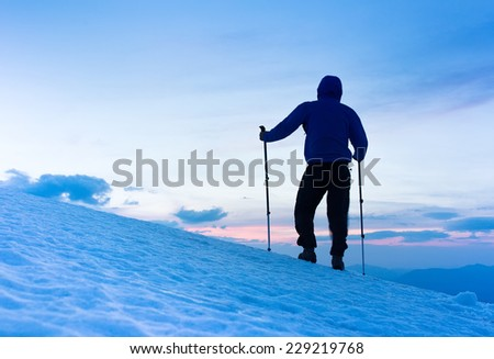 At dusk a brave backcountry skier reaching the summit of the mountain after a long day walking in the wilderness. Adventure and exploration concept. - stock photo