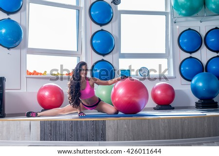 At gym. Smiling brunette doing stretching exercise - stock photo