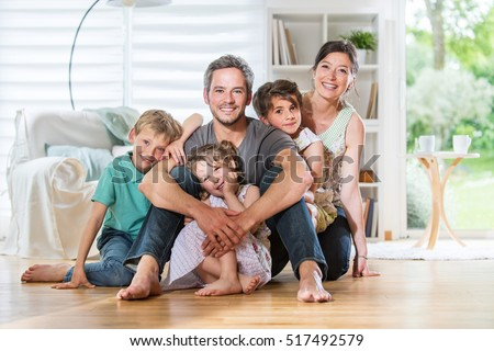 At home, Cheerful family of five persons sitting on wooden floor in the living-room. They are smiling while looking at camera